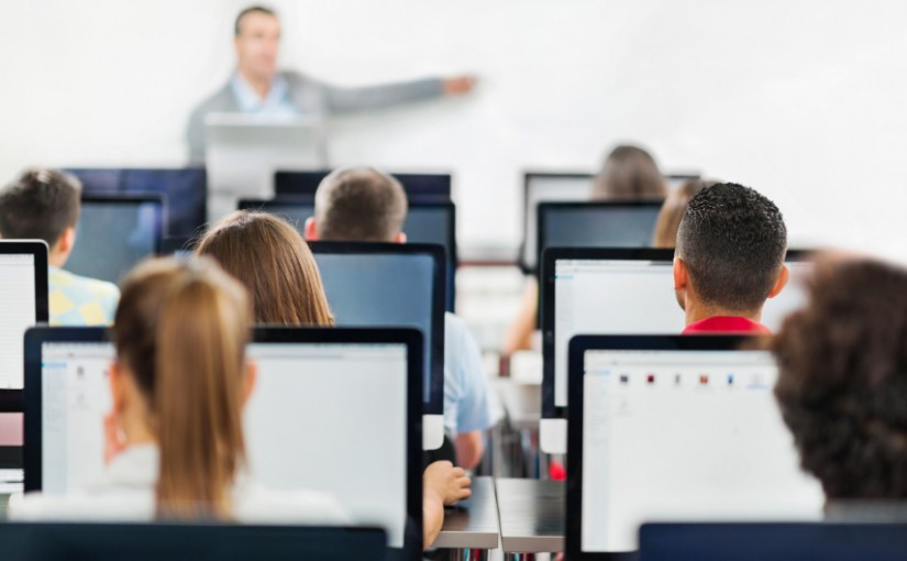 Rear view of group of people at a computer class. Teacher is teaching in the background.  [url=http://www.istockphoto.com/search/lightbox/9786738][img]http://dl.dropbox.com/u/40117171/group.jpg[/img][/url]